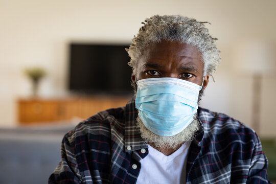 Portrait of Black African American senior man wearing face mask at home