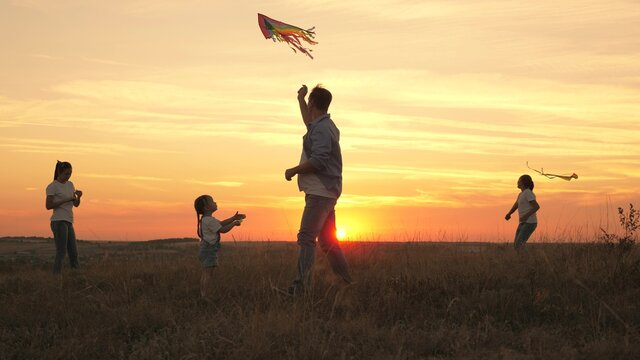 dad with children plays with kites at sunset in park. Outdoor family game. Daddy and healthy daughters are launching multi-colored paper resins into the sky. fun play with parents in sun