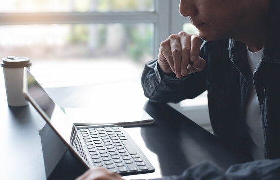 Pensive asian business man thinking while serious working on laptop computer from home office