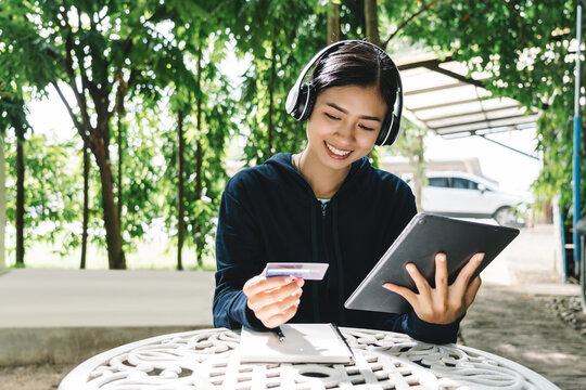 Young asian woman using credit card for buying something on tablet at cafe.