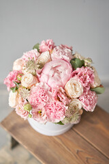 Beautiful spring bouquet in round box. Arrangement with various flowers. The concept of a flower shop. A set of photos for a site or catalogue. Work florist.