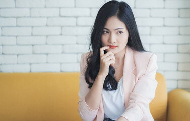 Asian woman thinking with finger near chin.