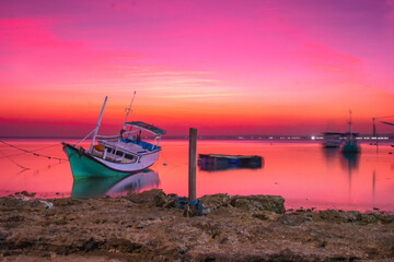 Beautiful view of a fishing boat under the pink sky