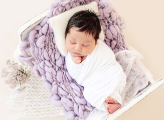 Funny newborn resting on tiny bed