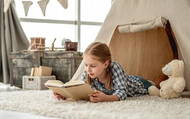 Cute little girl reading adventure book