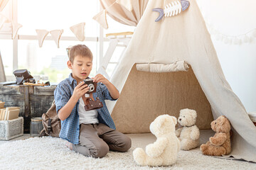 Little boy taking picture of plush teddy