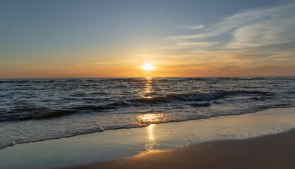 Zachód słońca na plaży w Egmond aan Zee, Holandia Północna.