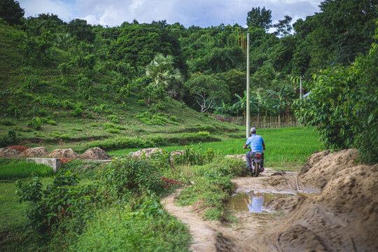 man riding a motorbike in rural bangladesh