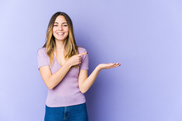 Young caucasian woman isolated on purple background excited holding a copy space on palm.