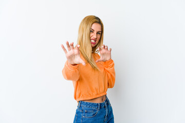 Young blonde woman isolated on white background showing claws imitating a cat, aggressive gesture.