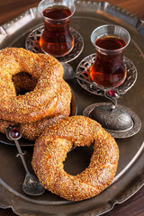 Turkish bagel simit and tea  in glass cup on wooden table