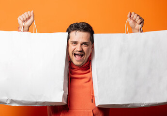 smiling guy in orange hoodie with shopping bags