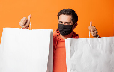 guy in face mask and with shopping bags