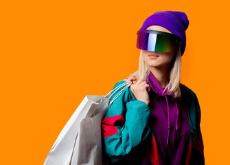 Style woman in 90s tracksuit and VR glasses with shopping bags