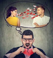 Stressed guy tearing in half red heart frustrated with girlfriend flirting with another man