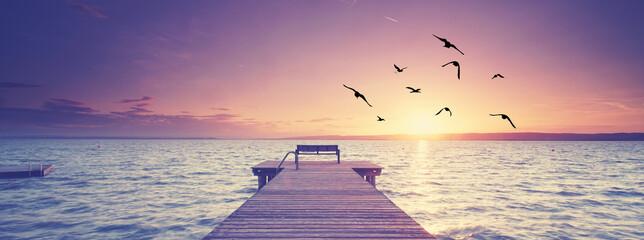schöner See im Sonnenuntergang mit Holzsteg