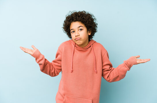 African american little boy isolated doubting and shrugging shoulders in questioning gesture.