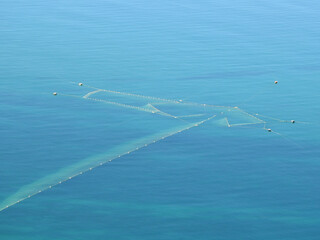 photograph of a large fishing net in the blue sea