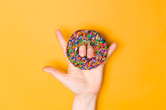 I love you hand sign with chocolate frosted donut with sprinkles, sugar-glazed frosted on yellow background. Playful and joyful tasty sugary comfort food for customer with copy space. Donut lovers.