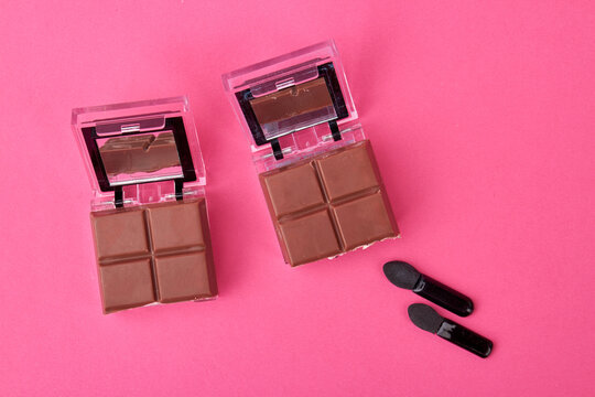 Cosmetic powder caces with chocolate. Concept of chocolate skincare mask. Isolated on pink background.