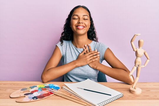 Young african american girl artist sitting at studio table smiling with hands on chest, eyes closed with grateful gesture on face. health concept.