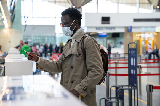 African American man stands at check-in counters at the airport terminal, giving passport to an officer. Flight rules during a Covid-19 pandemic only in a protective face mask. New normal concept.