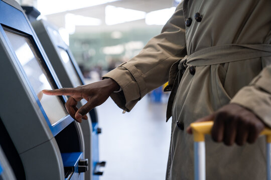 Black traveler man using self check-in machine kiosk service at airport, finger point on display. Close up.
