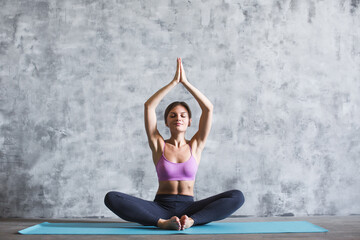 Young woman practicing yoga lotus position on blue mat indoors against gray wall.