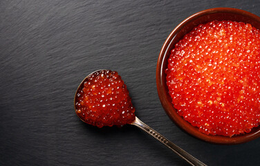 Red caviar in pot on stone plate.