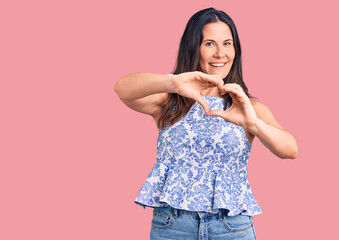 Young beautiful brunette woman wearing casual t-shirt smiling in love doing heart symbol shape with hands. romantic concept.