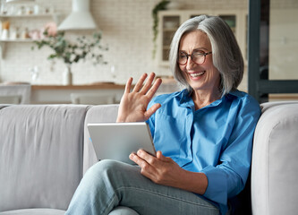 Fototapeta Happy 60s older mature middle aged adult woman waving hand holding digital tablet computer video conference calling by social distance virtual family online chat meeting sitting on couch at home. obraz