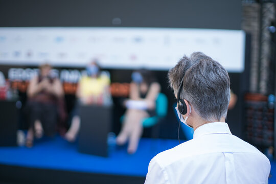 man with face mask and earphones watching a presentation event