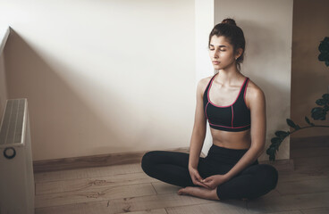Home yoga session done by a caucasian woman in sportswear meditating on the floor near free space