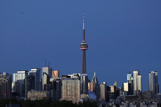 The CN Tower stands at dusk above office buildings and condominiums in the downtown core of Toronto
