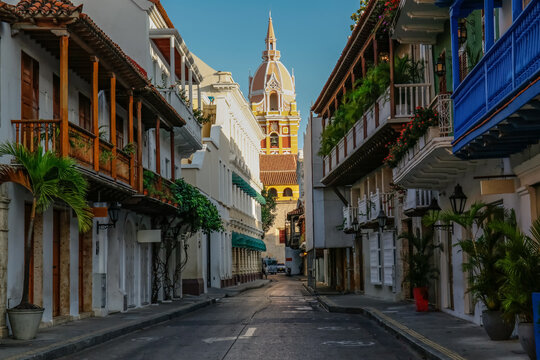 View to the clock tower of Cartagena cathedral with blue sky through a narrow street in shadow, Cartagena, Colombia, Unesco World Heritage