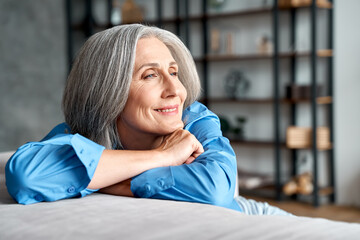 Happy relaxed mature old woman resting dreaming sitting on couch at home. Smiling mid aged woman relaxing. Peaceful serene grey-haired lady feeling peace of mind enjoying lounge on sofa and thinking. Wall mural