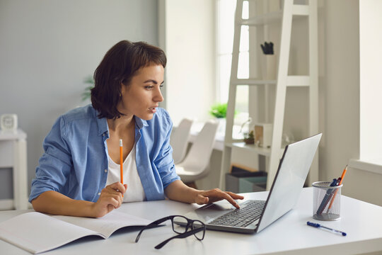 Woman talking to somebody and making notes during online conversation on laptop at home