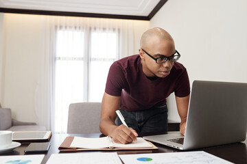 Serious young businessman in glasses checking e-mails or reports on laptop screen and taking notes in planner