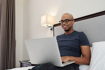Smiling young man in glasses sitting on bed and programming on laptop