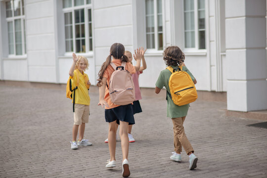 Schoolchildren in protective masks in the school yard greeting each other waving hands