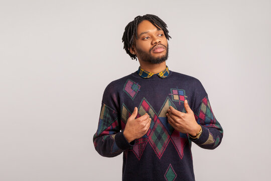 Self confident egoistic guy with dreadlocks pointing hands on himself with arrogant face, proud of start up. Indoor studio shot isolated on gray background