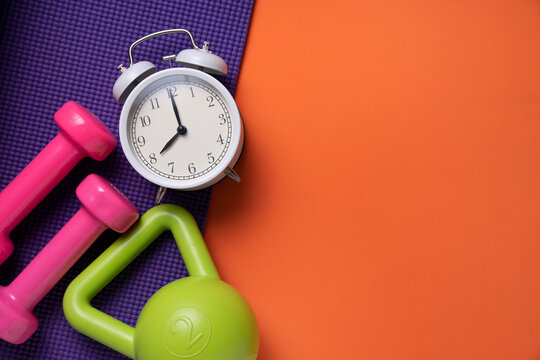 pink dumbbell, alarm clock, kettle bell and purple yoga mat on orange table background, fitness healthy and sport time concept