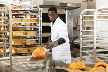 Experienced African American baker pulling freshly baked loaves from industrial oven on wooden shovel ..