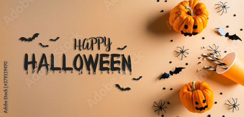 Halloween decorations made from pumpkin, paper bats and black spider on pastel orange background. Flat lay, top view with Happy Halloween text.