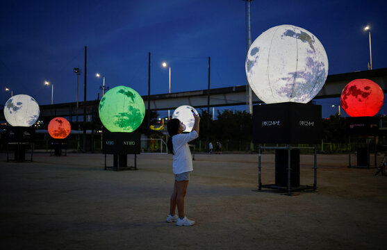 A girl takes a picture of artificial full moons, in Seoul