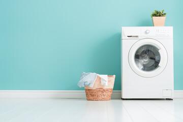 Obraz washing machine on teal wall background - fototapety do salonu