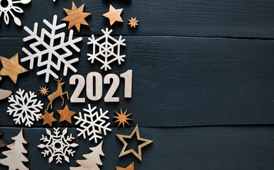 The beautiful christmas background with a lot of small wooden decorations and wooden numbers 2021...