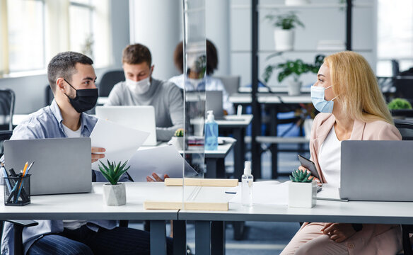 New normal and communicate with protection. Millennial man and woman in protective masks work with documents in protective glass