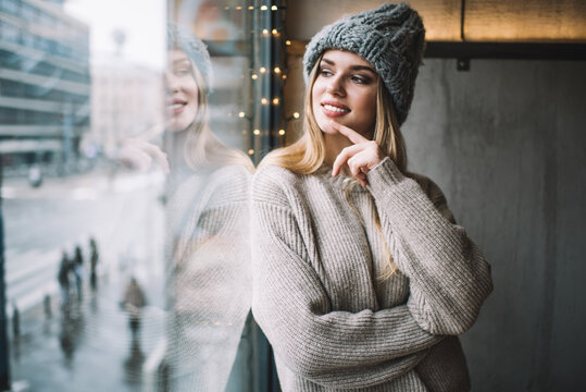 Contemplative female teenager dressed in stylish winter hat and knitted sweater looking at window and dreaming, happy Caucasian hipster girl 20 years old enjoying recreation and youth lifestyle