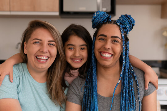 Portrait of brazilian gay couple with daughter looking at camera in kitchen home, indoors. Lgbtq family, bonding, love, generation concept..